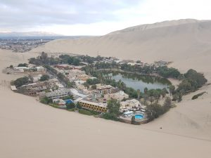 small town of huacachina around an oasis with sand dunes around and the andes mountains in the background