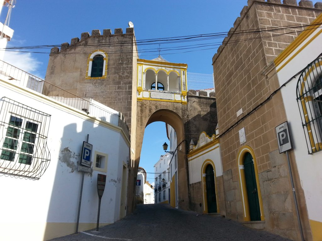 Manueline arch in white and yellow in between military structures in Elvas, Alentejo, Portugal