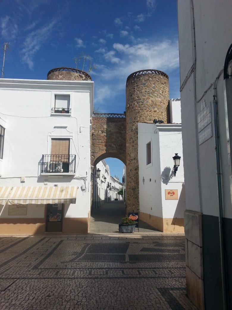 white and yellow houses in front of a stonewall gate in Olivença