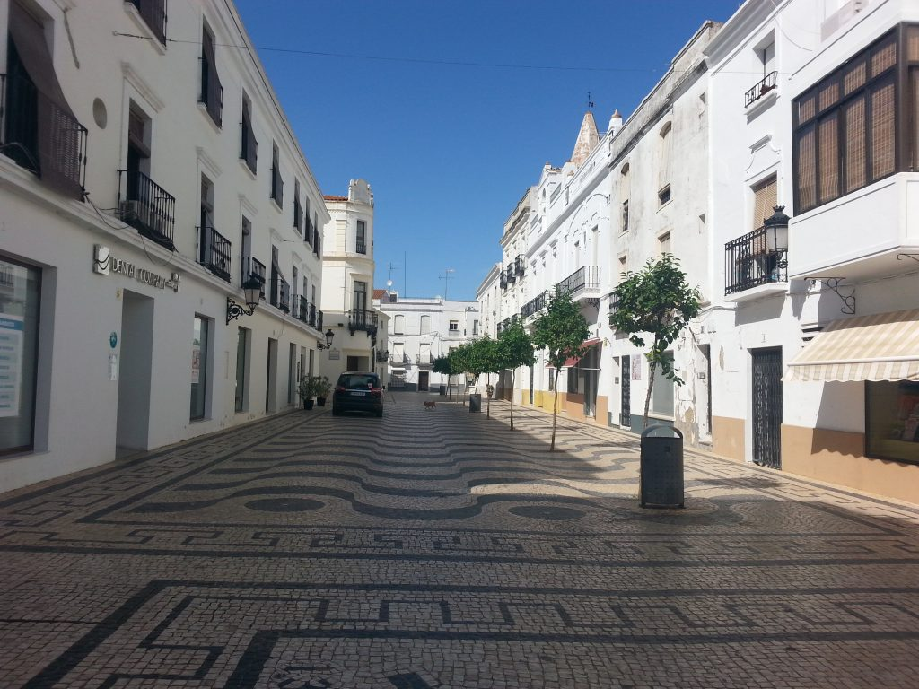 Typical Alentejo street with white houses in yellow skirting, Portuguese black and white limestone Pavament in Olivença
