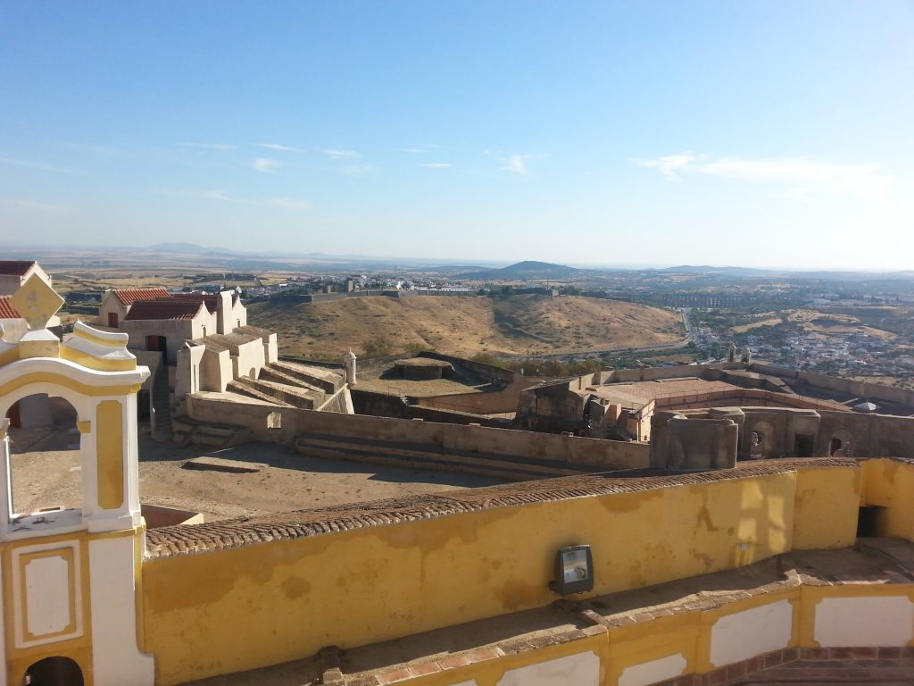 View from Senhora da Graça Fort: the walled city of Elvas stands atop a hill, with an aqueduct and a recent neighborhood to the right
