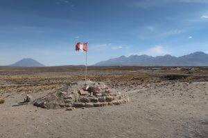 El Misti and Chachani volcanoes rise above the plateau behind a Peru flag nearby Arequipa